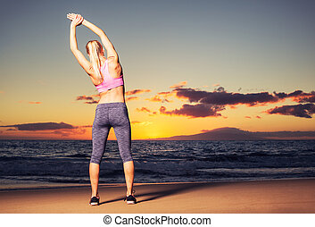 Woman stretching at sunset