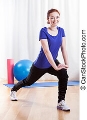 Woman stretching before training - Smiling woman stretching...