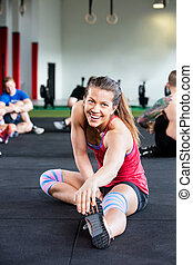Woman Stretching Exercise While Friends Sitting In Background