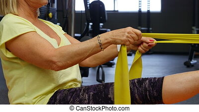 Woman stretching her legs with resistance band 4k