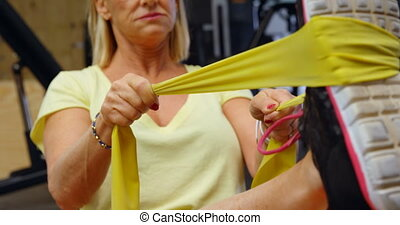 Woman stretching her legs with resistance band 4k - Woman...