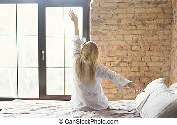 Woman stretching in bed after waking up