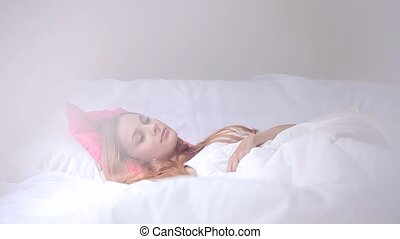 Woman stretching in bed at home