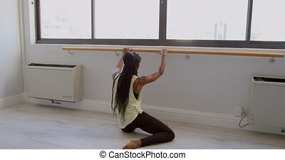 Woman stretching on barre in fitness studio 4k - Rear view...