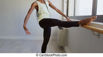 Woman stretching on barre near window 4k - Woman stretching...