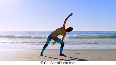 Woman stretching on beach 4k - Rear view of woman stretching...