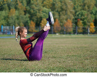 Woman stretching on the grass outdoor in a park.