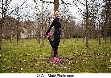 woman stretching right leg in park