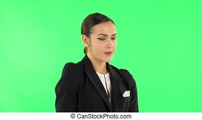 Woman strictly gesturing with hands shape meaning denial saying NO. Girl with dark hair wearing a black business suit at green screen at studio.