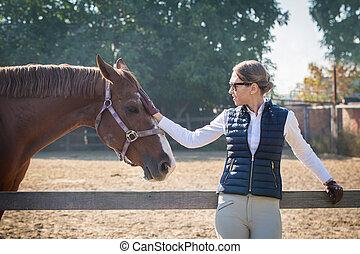 Woman strokes a horse