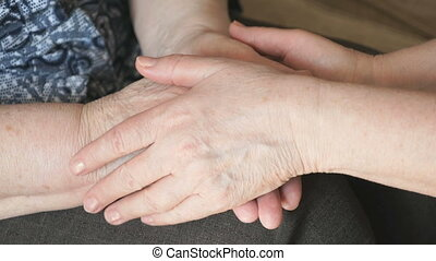 Woman strokes an old wrinkled woman's hand