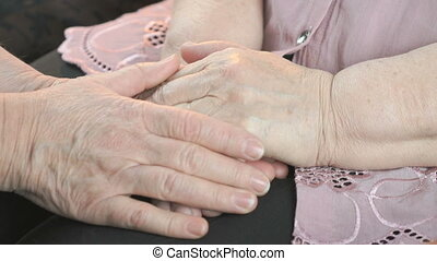 Woman strokes old woman's hands during illness - Woman...