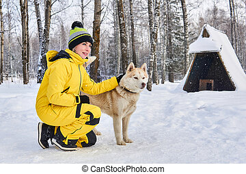woman stroking a husky dog in the winter forest