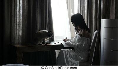 Woman stroking cat at laptop