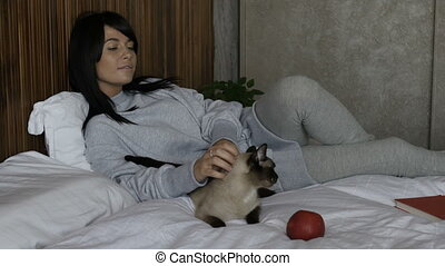 Woman stroking cat on bed