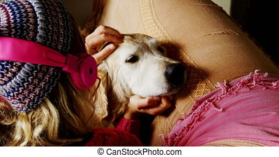 Woman stroking her dog on sofa at home 4k - Rear view of...
