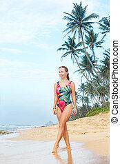 woman strolls along the ocean shore