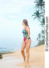 woman strolls along the shore