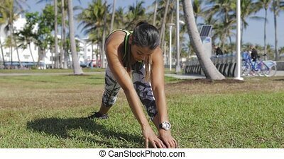 Woman strtching on lawn - Attractive young woman in...