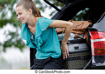 woman struggling to fit her luggage in a car