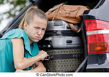 woman struggling to fix luggage in a car