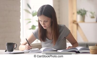 Woman student preparing for exam read textbook noting in notebook