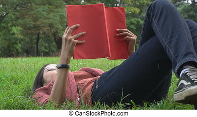 Slow motion shot of woman college student reading book in university park. Happy people reading book for studying or hobby reading in relax college garden.