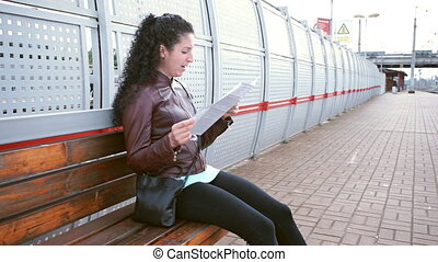 Woman studies a map and yawns. Waiting for train on platform
