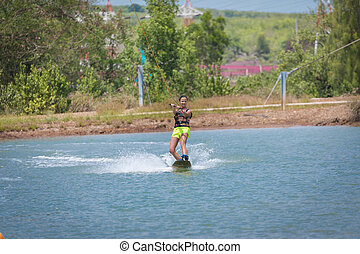 Woman study wakeboarding on a blue lake