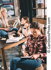 woman studying and writing in copybook with two students behind