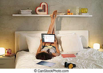 Woman Studying In Bed Doing Homework At Sunset