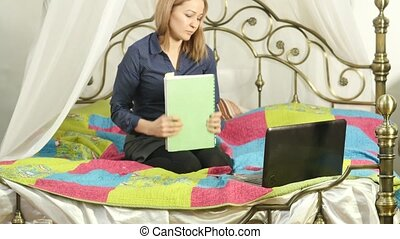 Woman studying on a bed with workbook and laptop. on-line education in home.