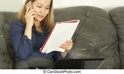 Woman studying on a sofa with workbook and laptop. on-line...