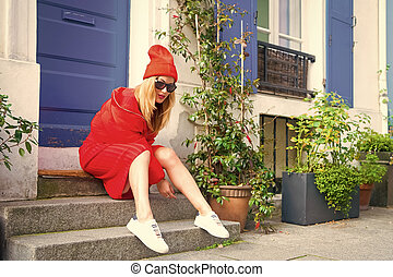 Woman stylish outfit sit on stairs near entrance house picturesque street in Paris. Paris known as capital of fashion confirms title stylish citizens. Changing trends keeps Paris magnet fashion world
