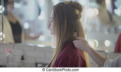 Woman stylist applies hairspray on hairdo in beauty salon.