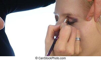 woman stylist puts dark eye shadow on eyelids of a blonde...