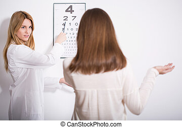 Woman suffering for myopia during eye exam