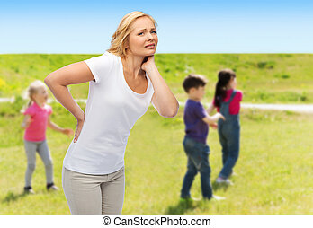 woman suffering from backache over group of kids - people,...