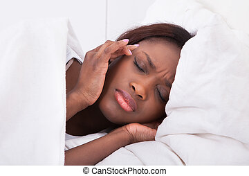 Woman suffering from headache in bed at home
