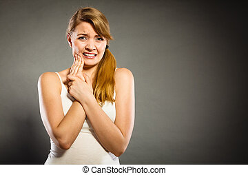 Dental care and toothache. Young woman achy girl suffering from terrible tooth pain, touching pressing her cheek by hand palm.