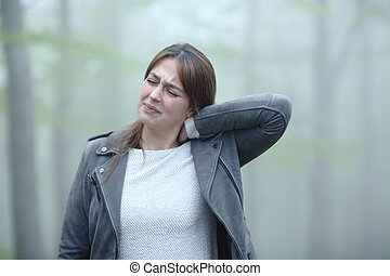 Woman suffering neck ache in a foggy forest