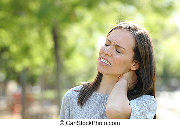 Woman suffering neck ache outdoors in a park
