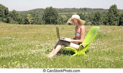 Woman sunbathing and working
