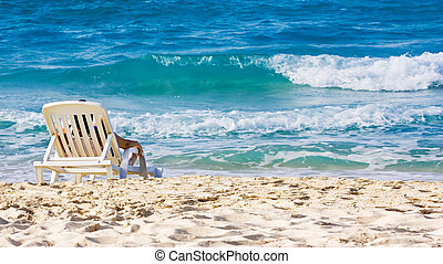 Woman sunbathing in a plastic chair on a beautiful beach in Cuba