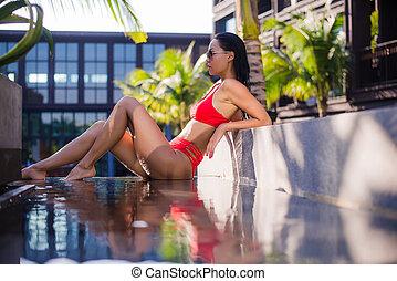 Woman sunbathing in bikini at tropical travel resort. Beautiful young woman lying near pool.