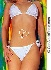 Woman sunbathing in white bikini with suntan lotion heart -...