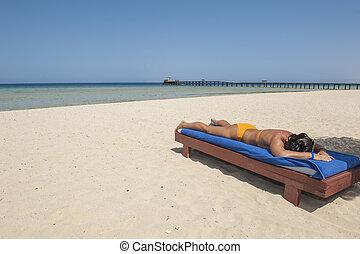 Woman sunbathing on a tropical beach