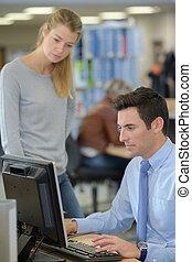 woman supervising man using computer