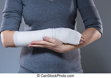 Woman support her hand in bandage