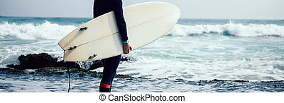 Woman surfer with surfboard going to surf